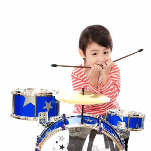 Asian young boy playing drum on white background